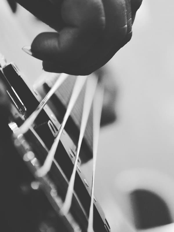 Gros plan sur les doigts d'un bassiste durant un cours de basse dans l'école Groove Lab
