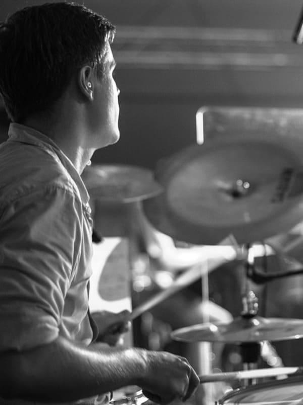 Un homme jouant de la batterie après avoir pris des cours de batterie dans l'école Groove Lab