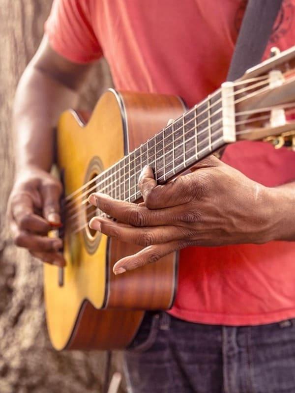 Un homme jouant de la guitare après avoir pris des cours de guitare dans l'école Groove Lab