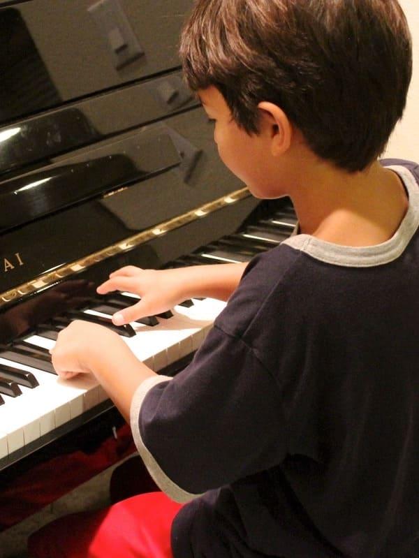 Un petit garçon jouant du piano après avoir pris des cours de piano dans l'école de musique Groove Lab